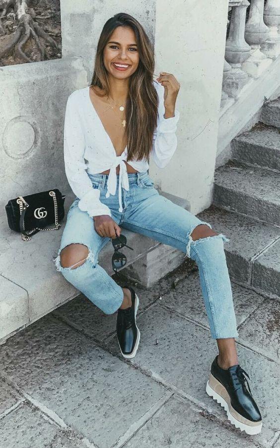 10 Ideias para usar jeans destroyed na próxima estação. Cropped com nozinho branco, calça jeans  com rasgo no joelho, tênis plataforma
