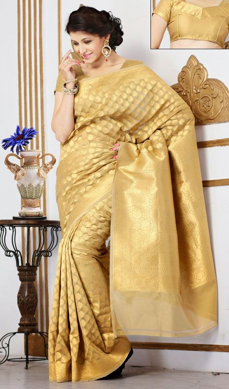 Gold Color Embroidered Banarasi Silk Saree Add grace and charm in this gold color Banarasi silk saree. This attire is displaying some really mesmerizing and creative patterns embroidered with self work. Comes with a matching stitched round neck blouse with 6 inches sleeves.  #BanarasiSilkSaree #BuyCottonSilkSareeOnline
