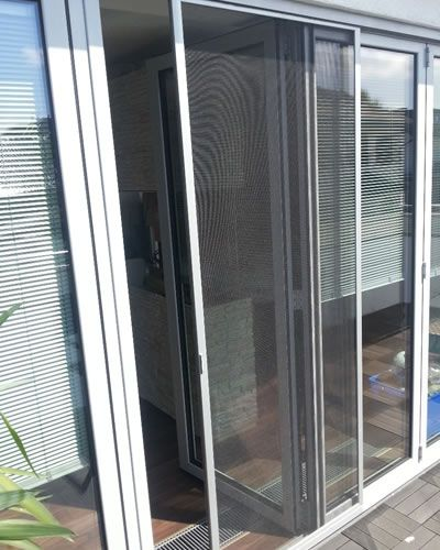 The Picture Shows A Sliding Door Whose Screen Is Pushed To Be Partially Open