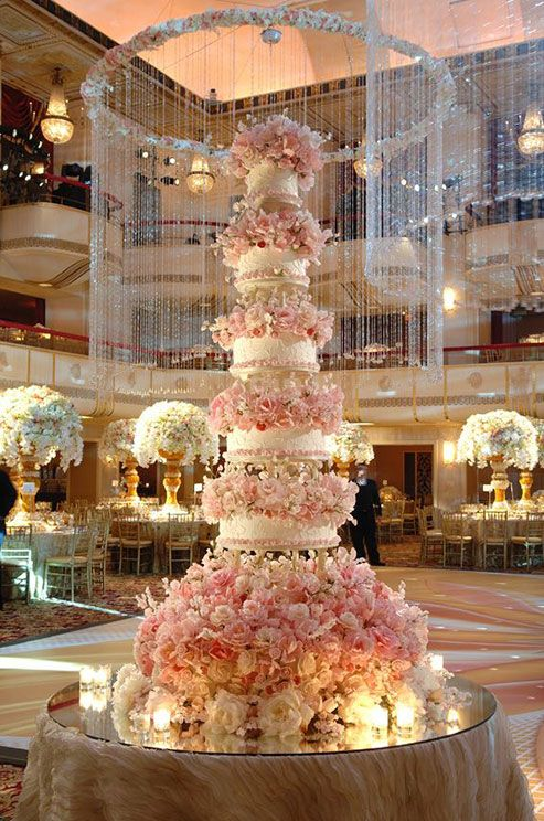 A jaw-dropping five tiered wedding cake by Sylvia Weinstock rests atop a bed of blooms and candles.