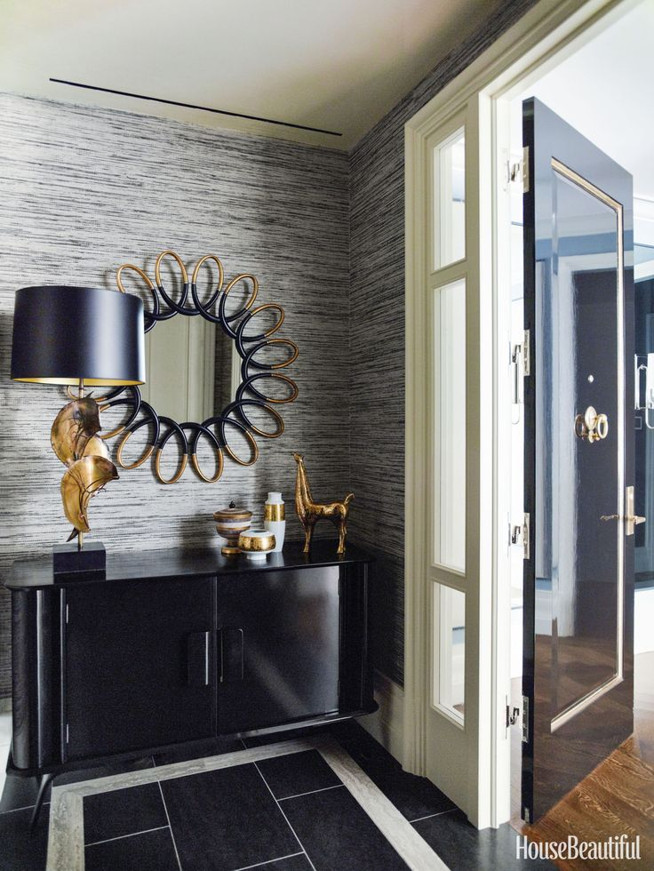 """""""I love having some fun in an entry,"""" Mendelson says. A Brutalist lamp stands on a vintage black lacquered cabinet. Phillip Jeffries's Mystic Weave wallcovering shows off a mirror from Interiors by Royale. - HouseBeautiful.com"""