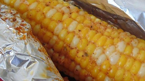 Husked ears of corn are coated in a paste made with mayonnaise, Parmesan cheese, chili powder, parsley, and black pepper before being wrapped in aluminum foil and roasted in the oven for a new way to prepare everyone's favorite summertime barbeque side item.