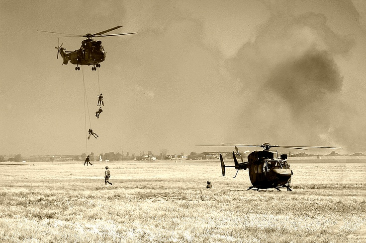 Drop-off choppers arriving in the war zone lowering soldiers to the ground. Bracing them for battle