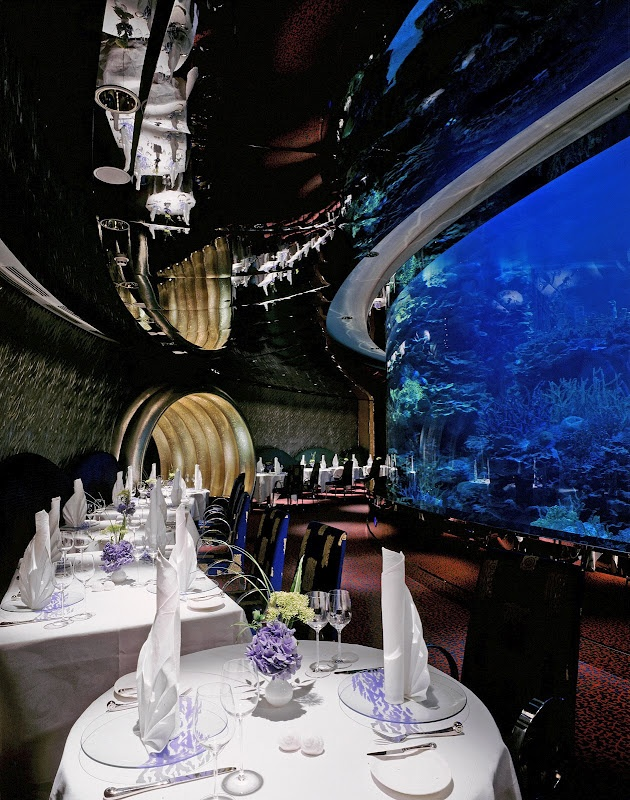 Al Mahara - Burj Al Arab restaurant Dubai  The dining experience at the Burj Al Arab's signature restaurant 'Al Mahara' is unique. This underwater themed restaurant begins with a mock submarine ride from the reception to the dining area. The tables are situated around a giant glass aquarium full of fish that adds to the restaurants submerged theme.