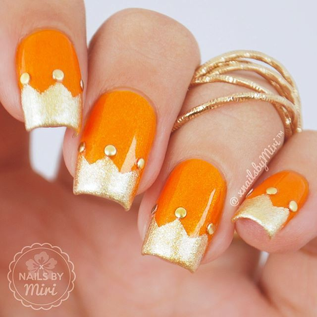 Orange nails with gold crown nail tips
