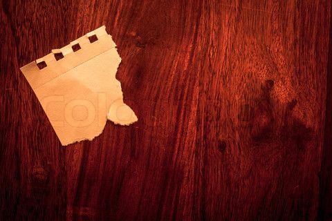 Stock image of 'Piece of torn paper on solid wood'