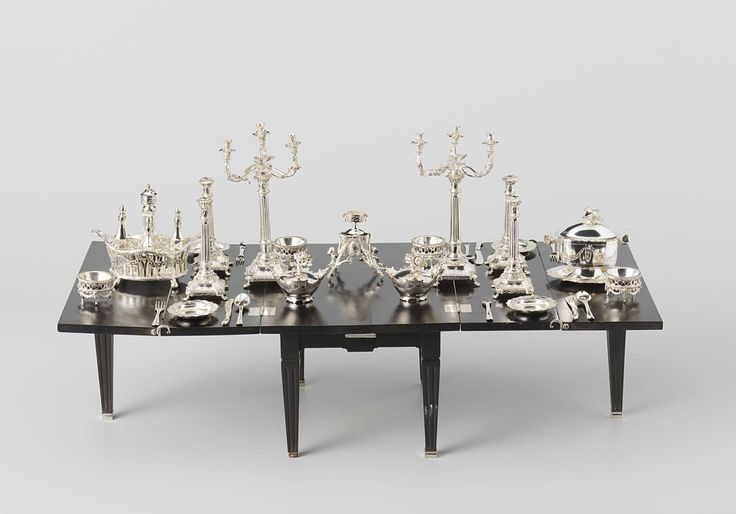 Silver table services were an unprecedented luxury in the Netherlands during the 18th century. The design of this miniature service, complete apart from the sauce bowls, is exceptionally fashionable. The candelabra are fully Neoclassical in style, with their foliate motifs, swags and decorative friezes derived from Classical architecture. The same motifs recur on other parts of the service.