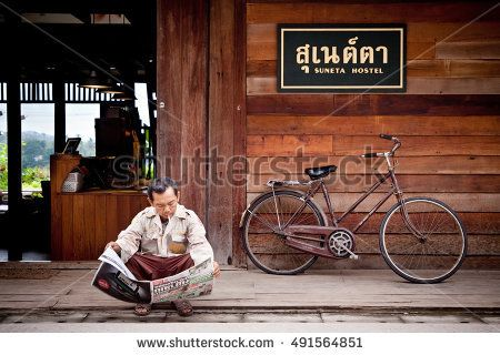 Loei, Thailand, - July, 02, 2011 : Unidentified Man Sit and read newspaper in front of the entrance to one of the hostels in Chiang Khan, Loei, Thailand.