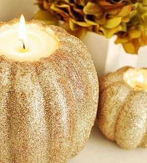Gotta have!  These would be great for center pieces with the orange and purple flowers. Could use the big gold pumpkin as a vase and then have a few smaller glittery gold/black pumpkins as candle holders (like in this picture)