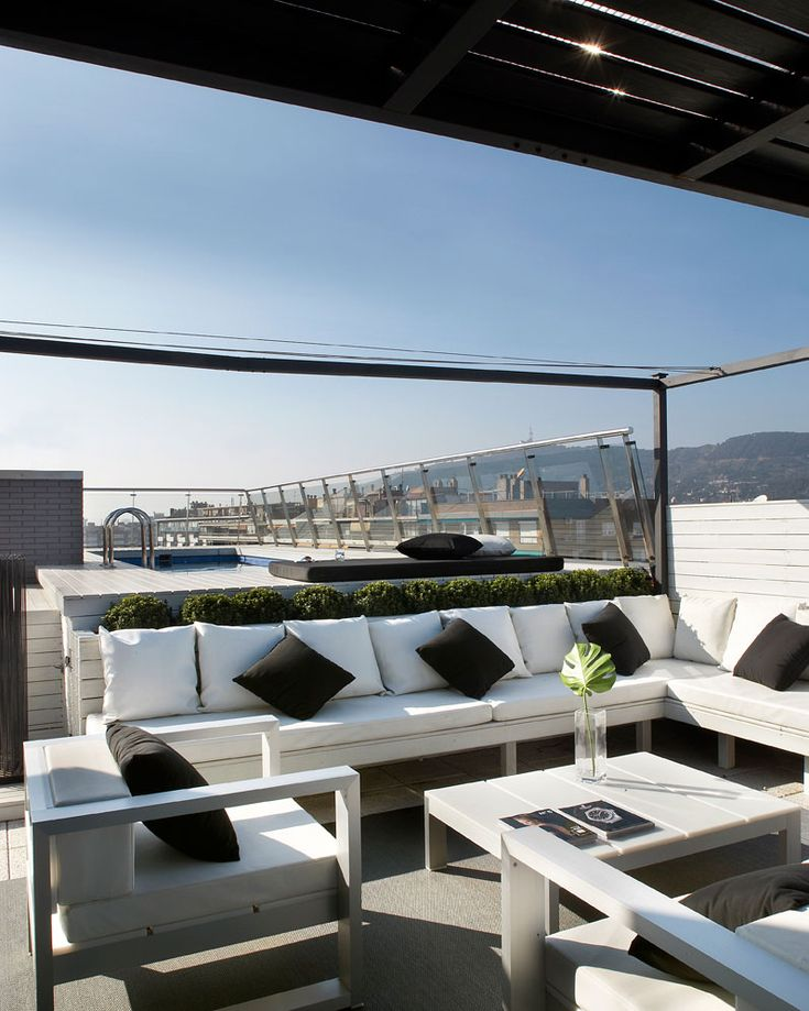 rooftop terrace - fabulous white styling for a patio - horizontal wood panels, raised buxus (box) balls