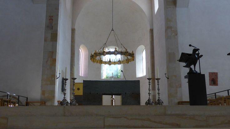Der neue,  aus drei mächtigen Steinblöcken als Verweis auf die alttestamentlichen Opferaltäre gestaltete Hauptaltar dient als Ort des Messopfers.Der Hauptalter des Hildesheimer Doms. Er korrespondiert mit dem Godehardschrein in der Krypta als Erinnerungsort an den ersten heilig gesprochenen Bischof von Hildesheim. Darüber der für diesen Raum gestiftete Radleuchter des Bischofs Thietmar (1038-1044) .