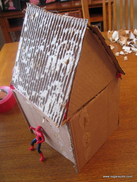 Create a Candy-less Gingerbread House from cardboard. Add lots of crafting materials (yarn, pom-poms, pipe cleaners twisted into candy canes...) part of the **25 Days of Christmas Play** series.