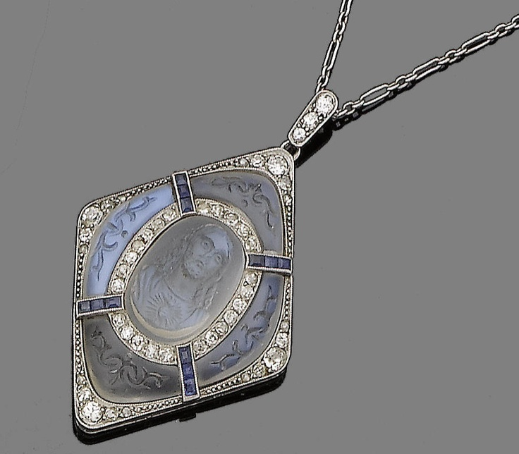 A moonstone, sapphire and diamond pendant necklace, circa 1915  The lozenge-shaped plaque, centrally-set with an oval-shaped moonstone cameo carved to depict Christ, within a single-cut diamond border, to a further surround of foliate carved moonstones, highlighted with calibré-cut sapphires, old brilliant, single and rose-cut diamonds, to a fetter-link chain, diamonds approx. 0.70ct total, French assay mark,Edwardian, Diamonds Approx, Pendants Necklaces, Carvings Moonstones, Diamond Pendant, Calibré Cut Sapphire, Diamonds Border, Opals Moonstones, Diamonds Pendants
