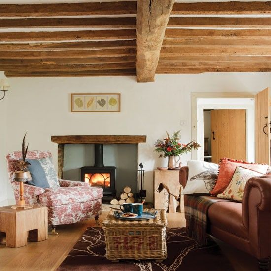 Cosy country living room   This country living room mixes leather with patterned upholstery to create a cosy look. The beams add instant warmth to the room, while white walls stop them from being overbearing.   Table Liberty Armchair fabric Lewis & Wood  Read more at http://www.housetohome.co.uk/living-room/picture/cosy-off-white-and-wood-living-room#5d2MbmihdxDPlBPe.99
