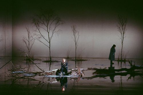 Eugene Onegin at English National Opera - Stylized Realism - There are realistic elements in the set, but there are heightened elements through the use of light and the reflections shown on the floor