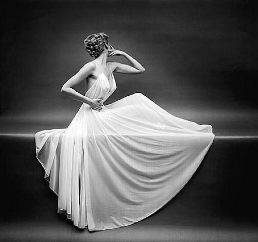 I love the complete simplicity of the photo and how it completely exudes femininity and elegance. You can draw your own conclusions based upon the woman's hair, pose, dress, and even fabric of the dress. It says so much while being minimalistic. Gorgeous.  Mark Shaw (1954)