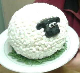 I used hemisphere pans (from Lakeland) to create this circle cake. I iced it with Betty Crocker frosting and added mini marshmallows all around it for the wool. The head is made from fondant.