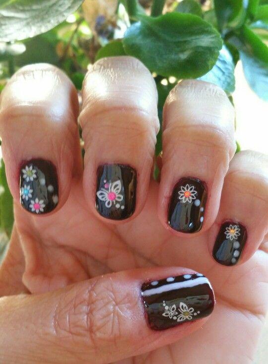 Diseño de uñas con color oscuro y decorado con flores y mariposas