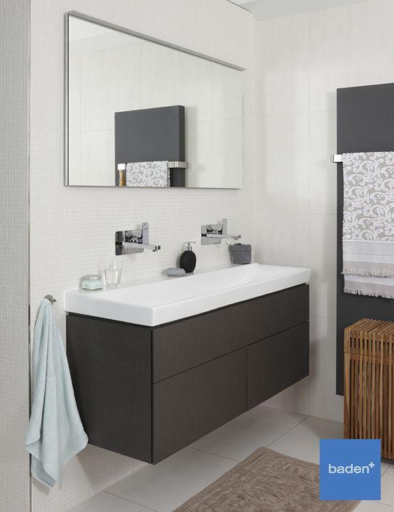 Het donkere wastafelmeubel in deze luxe Off White badkamer van Baden+ vormt een prachtig contrast met de crème witte tegels.