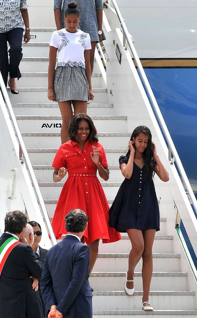 Red, White & Blue! Michelle, Malia and Sasha Obama Arrive in Venice, Continue Their European Chic Streak!    Michelle Obama and daughters Sasha Obama and Malia Obama touched down in Venice, Italy on June 19 wearing a patriotic medley of swingy summer frocks: Michelle in a rich red shirtdress, Malia in a short navy blue frock and Sasha sporting a structured white top and monochrome skirt.