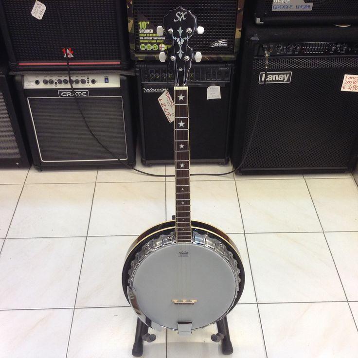 Banjo economico di marca SX. Pelle Remo, fondo Curly Malapoga, manico in mogano e tastiera in palissandro. Corde D'Addario.