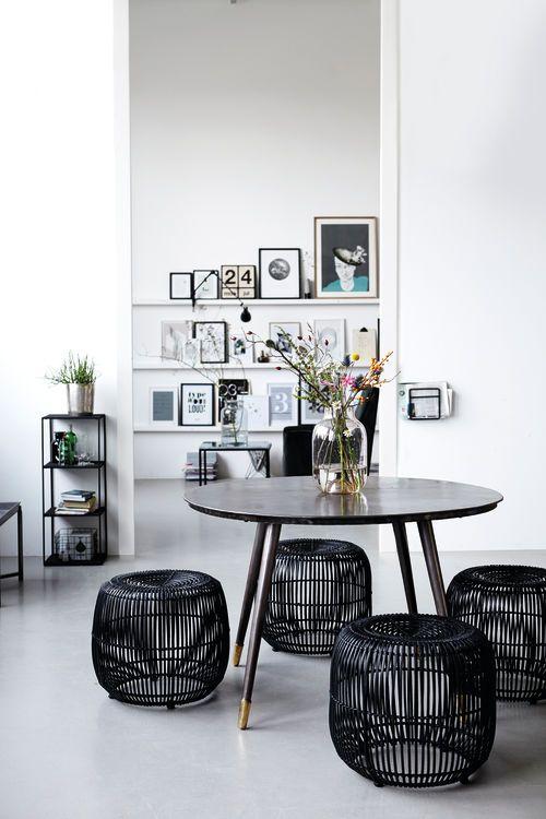 Mooi beeld van lichte kamer met donkere meubels van het Deense merk House Doctor; een zwarte ronde tafel, zwarte rotan krukjes en een zwart wandkastje.
