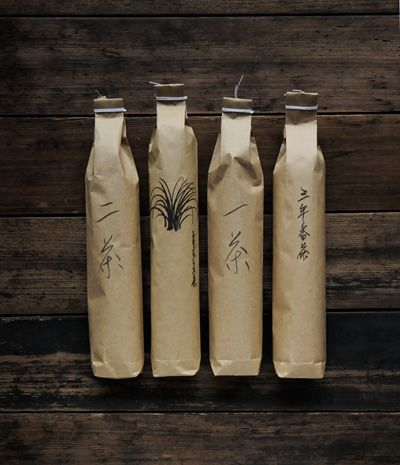 thin/elongated bottles wrapped in plain brown paper with chinese characters on the side + closed with white twine