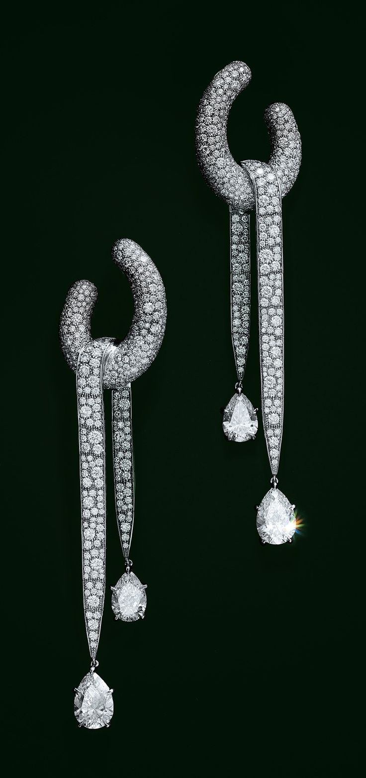 Earrings in platinum with pear-shaped and round brilliant diamonds.