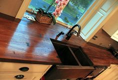 """Copper sink with """"wood"""" concrete countertops and cream/yellow cabinets"""