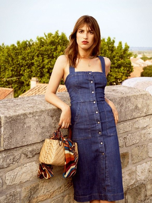 A button-down denim dress is worn with a necklace and straw structured bag.