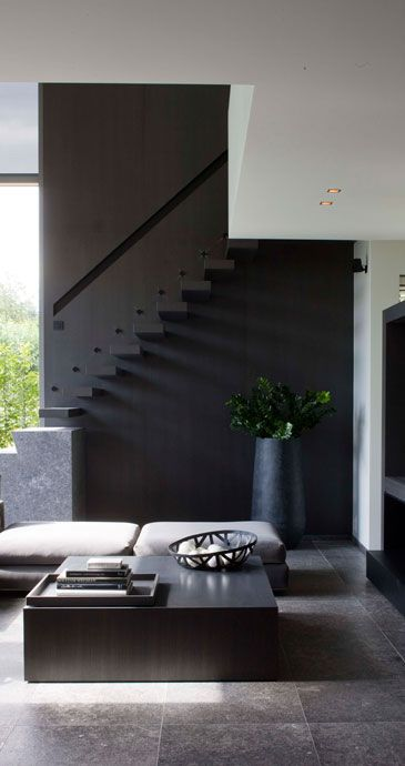 | STAIRS | INTERIORS | adore the interior detail work of interieurarchitect Frederic Kielemoes. Image Credit: http://www.frederickielemoes.be/#  When using a simple colour palette to colour block vertical features in volumes of space with high ceilings, less is more.  I'm a true believer in less contrast between surface finishes to provide a much more subtle yet elegant elevation.  #stairs #black #wood #graysFloating Stairs, Black Interiors, Interiors Design, Frederic Kielemoes, Modern Living Room, High Ceilings, Interiordesign, Dark Wall, Black Wall