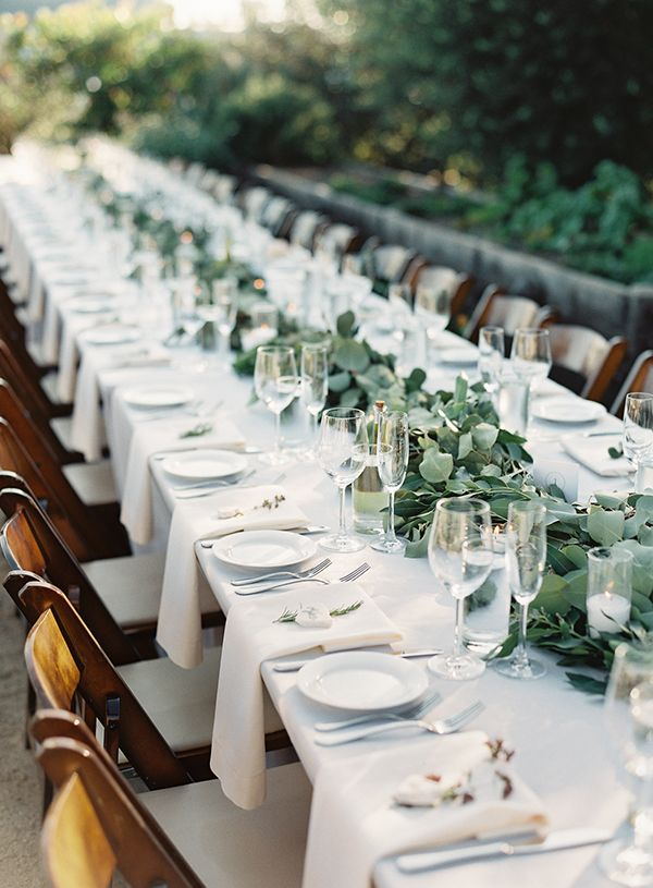 Flat ropes of greenery, small white flowers, candles, glass elements, and longest table you can fit.