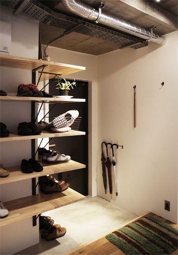 壁付けの造作棚でコーナーまで収納に活用。視線の抜けもあって玄関すっきり。ハンガーバーを使った傘立てにも着目。
