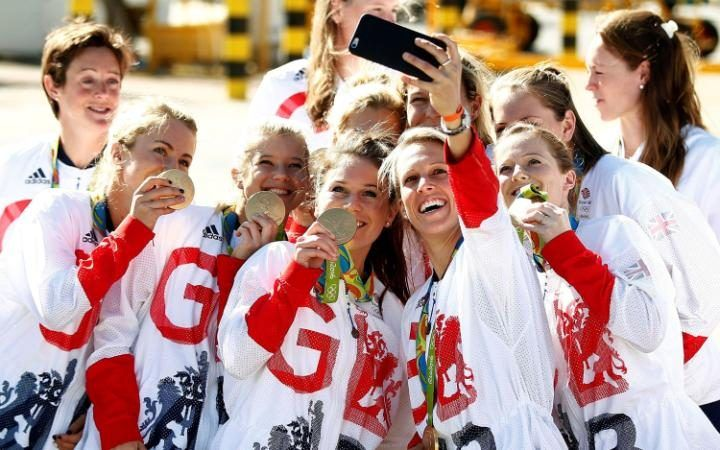 Team GB athletes pose with their medals for selfies at Heathrow