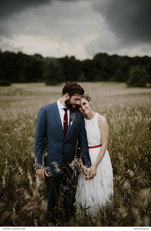 Intimate wedding couple shot with the bride in a relaxed white dress and red belt and the groom in a neat navy suit with a deep red tie!