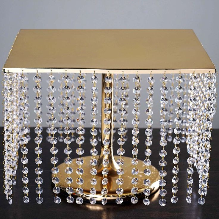 """16"""" Bejeweled Gold Square Crystal Beaded Stainless Steel Chandelier Wedding Cake Stand / A true emblem of luxury and style! Our elegant gold bling cake stand is adorned with sparkly leaded cut crystals wired into place and designed with detailed attention. Add a touch of glitz and glam to your table settings with this bejeweled cake dish that is topped with reflective metal for a beautiful display."""
