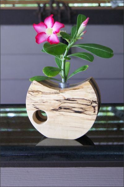 This handcrafted wooden bud vase holds precious buds of your favorite flowers. Dress up the vase with a single flower for a beautiful display. Featuring a variety of hardwoods and shapes these bud vases will add the perfect finishing touch to any room in your home. The flower bud tube holds water and is inserted into the center of the wooden vase. A truly extra special gift for many occasions. http://woodsmithofnaples.com/wooden_bud_vase_2.html