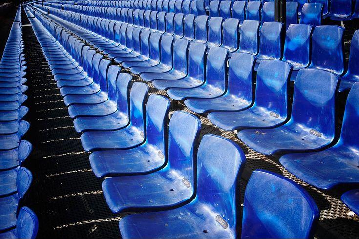 Je ziet hier een herhaling van blauwe stoelen op een rij.
