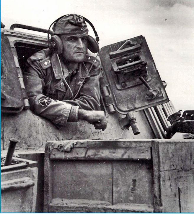 A Stug 3 commander looks out the rear hatch of his tank