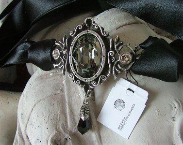 Handgemaakt choker ketting geinspireerd op 18eeuws barok met een grote antraciet Swarovski diamantkristal en twee kleine blanke swarovski kristallen.  Afmeting Ornament: 7 x 7 cm lang. Breedte lint...