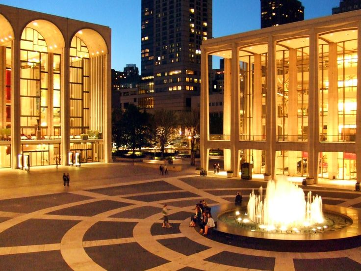 Looking northwest at Lincoln Center.  From left:  The Metropolitan Opera, people at the fountain, Avery Fisher Hall.