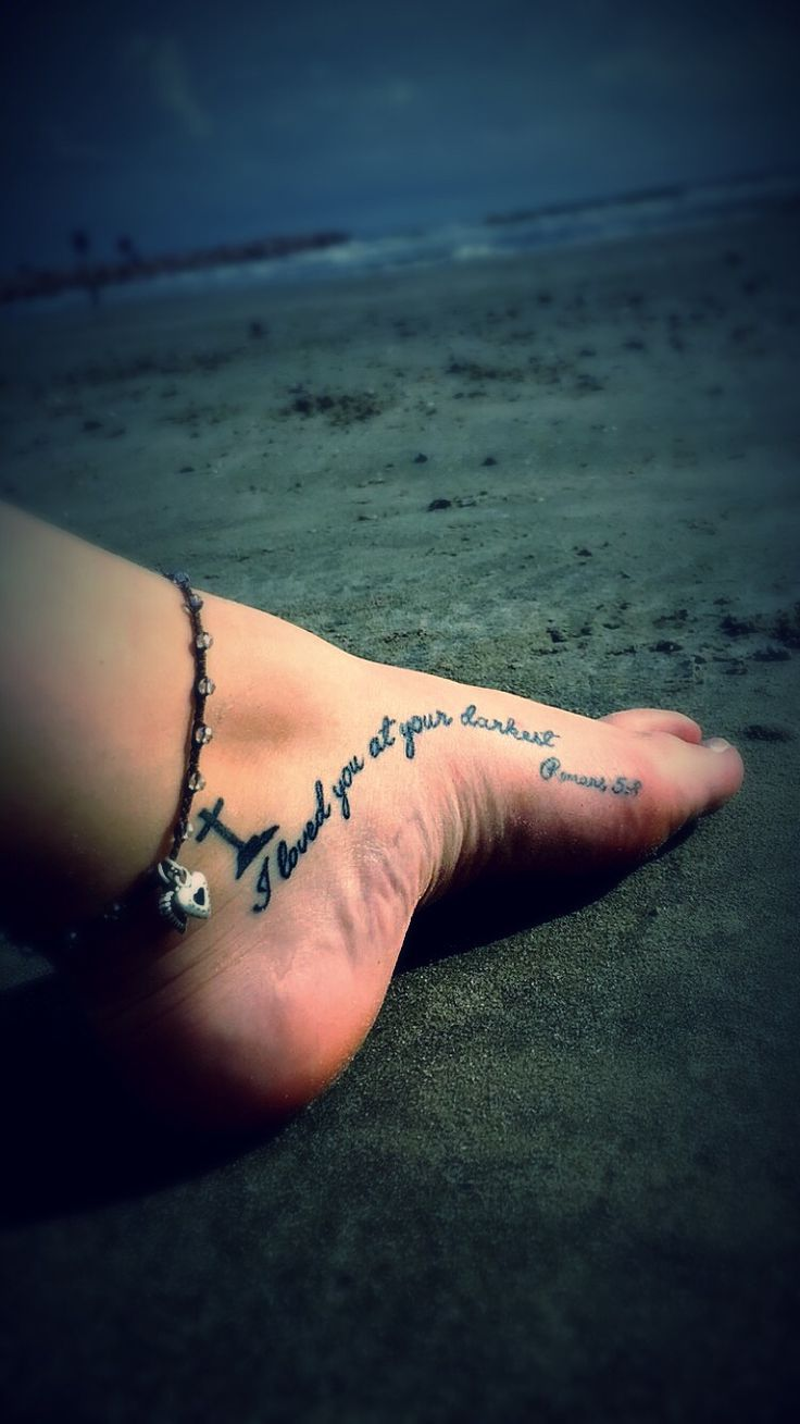 I loved you at your darkest Romans 5:8 bible verse foot tattoo with cross on ankle.