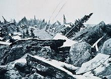 The 1964 Alaska earthquake, magnitude 9.2,  began at 5:36 P.M. AST on Good Friday, March 27, 1964. Across south-central Alaska, ground fissures, collapsing buildings, and tsunamis resulting from the earthquake caused about 143 deaths (9 from quake, others from tsunamis) .  Lasting nearly four minutes, it was the most powerful recorded earthquake in U.S. and North American history.  The largest landslide in Anchorage occurred along Knik Arm between Point Woronzof and Fish Creek.