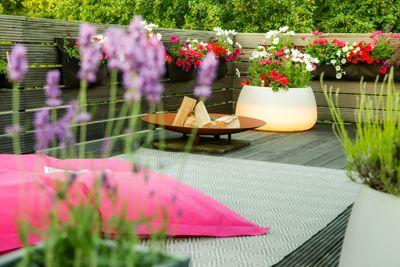Das Trio aus Feuerstelle, Pflanztasche und Leuchtkübel mit dem Sitzsack bilden Stimmungsvolle Komponenten für die Terrassennutzung.