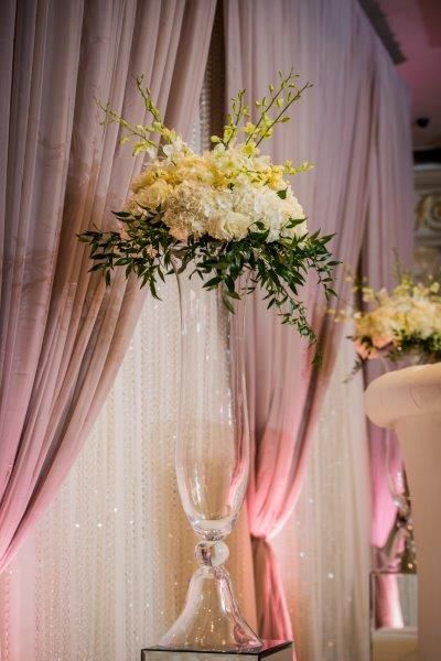 Tall clear vases, topped with a flower arrangement of white roses, hydrangeas and greenery http://www.fusion-events.ca/