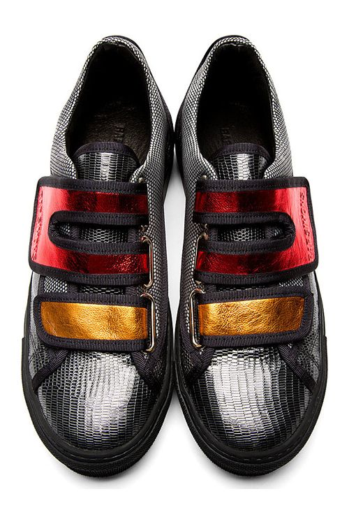 Lizard skin-embossed leather sneakers in metallic gunmetal grey. Black grosgrain trim throughout. Round toe. Foldover Velcro straps at vamp in metallic red and orange. Woven textile panelling at collar and eyerow in black and white. Buffed leather panel at heel in grey with embossed 'R' logo at heel collar. Designed by Raf Simons x Sterling Ruby.  http://zocko.it/LD2t9