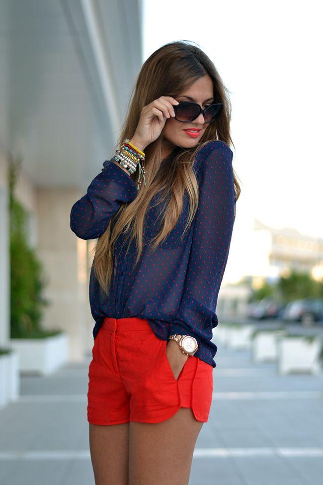 Comprar ropa de este look:  https://lookastic.es/moda-mujer/looks/blusa-de-botones-pantalones-cortos-gafas-de-sol-reloj-pulsera/2661  — Blusa de Botones a Lunares Azul Marino  — Pantalones Cortos Rojos  — Reloj Dorado  — Gafas de Sol Negras  — Pulsera Multicolor