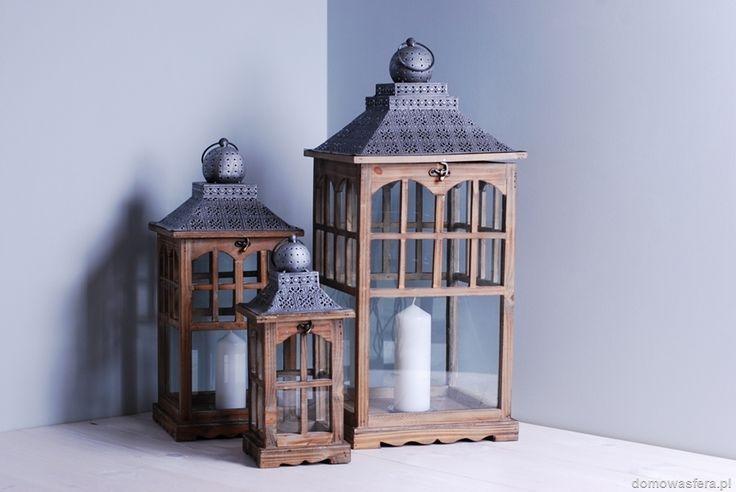 Komplet trzech dużych latarni wykonanych z drewna. Lampiony posiadają szklane okienka, metalowy gęsto perforowany daszek oraz metalowy talerzyk na dnie w celu uniknięcia rozlewania się wosku po całym lampionie.
