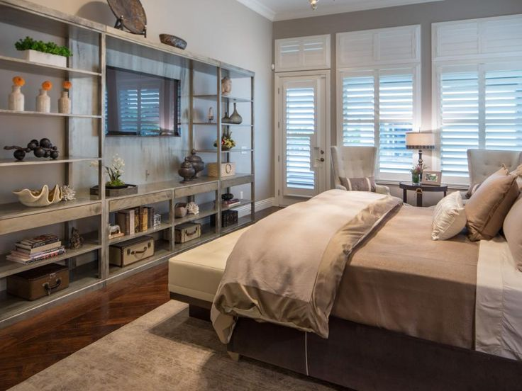 Keeping with the room's neutral color palette, distressed bookshelves add warmth to the large bedroom. To fill out the space and give the room a homey vibe, a pair of pretty white chairs were placed by the window.
