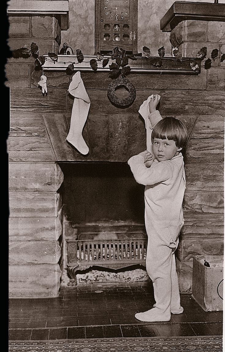 Hanging Christmas stockings by the fireplace, 1920s